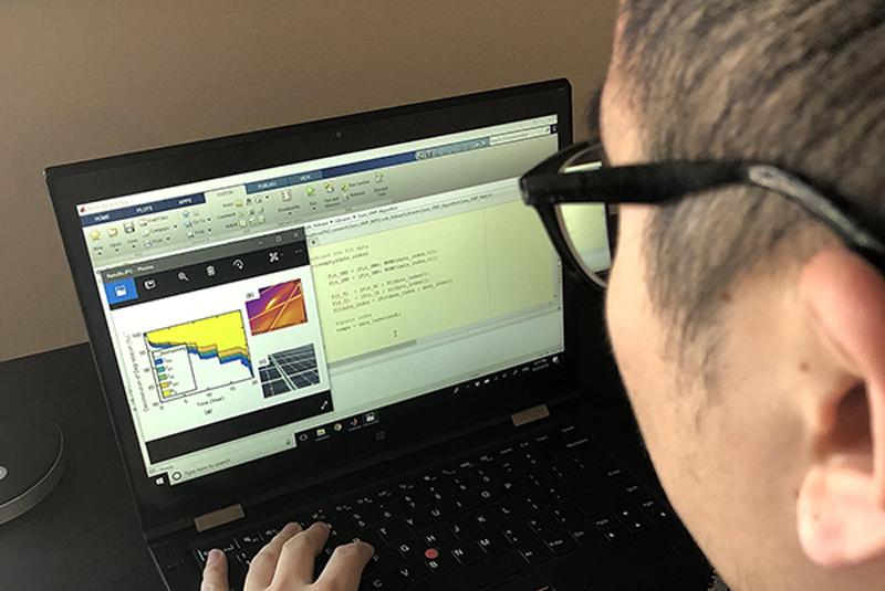Investigador de la Universidad de Purdue ante una curva generada por el algoritmo desarrollado para analizar la degradación de los paneles solares causada por el efecto del clima.