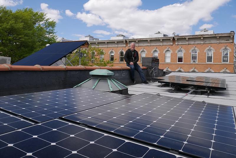 Miembro de Microgrid Brooklyn posando junto a paneles fotovoltaicos.