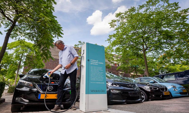 Un hombre carga su coche eléctrico, imagen que forma parte de la portada del documento del Tribunal de Cuentas Europeo.