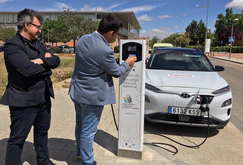 Presentación del nuevo punto de recarga semirrápida para vehículos eléctricos del Parque Científico y Tecnológico de Castilla-La Mancha. Un hombre manipula el poste de carga mientras otro le observa, para dar comienzo a la recarga de un vehículo con el enchufe ya puesto.