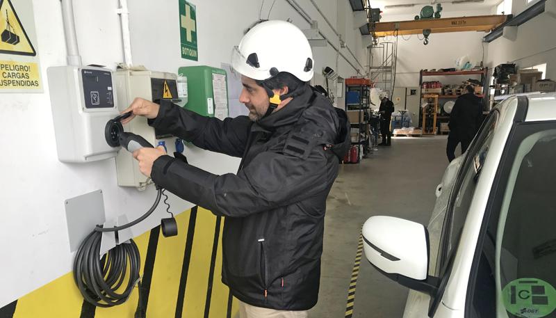 Un operario instala un punto de recarga para vehículos eléctricos en una nave o garaje.
