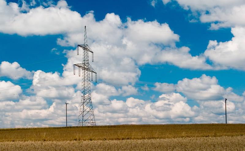 Un campo con una torre de electricidad.
